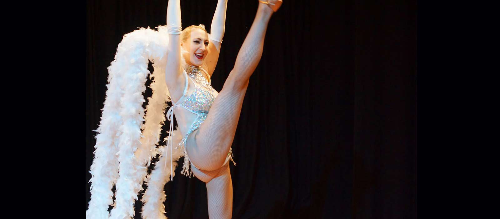 Las Vegas showgirl kicking leg high in silver costume