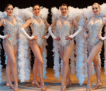 Las Vegas Showgirls in silver and white costumes with feather collars