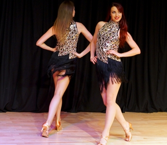 Two dancers in silver and black costumes