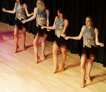 Four dancers in silver and black costumes