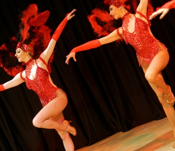 Las Vegas Showgirls  in red costumes with feather headpiece