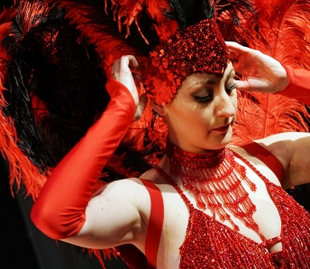 Las Vegas Showgirls in red costume and feather headpiece