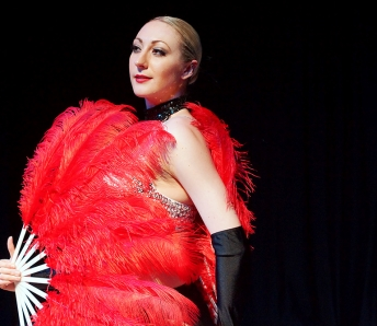 Las Vegas Showgirls in red costume and feather fan