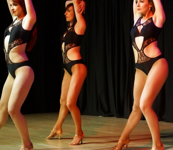 Three dancers in black costumes
