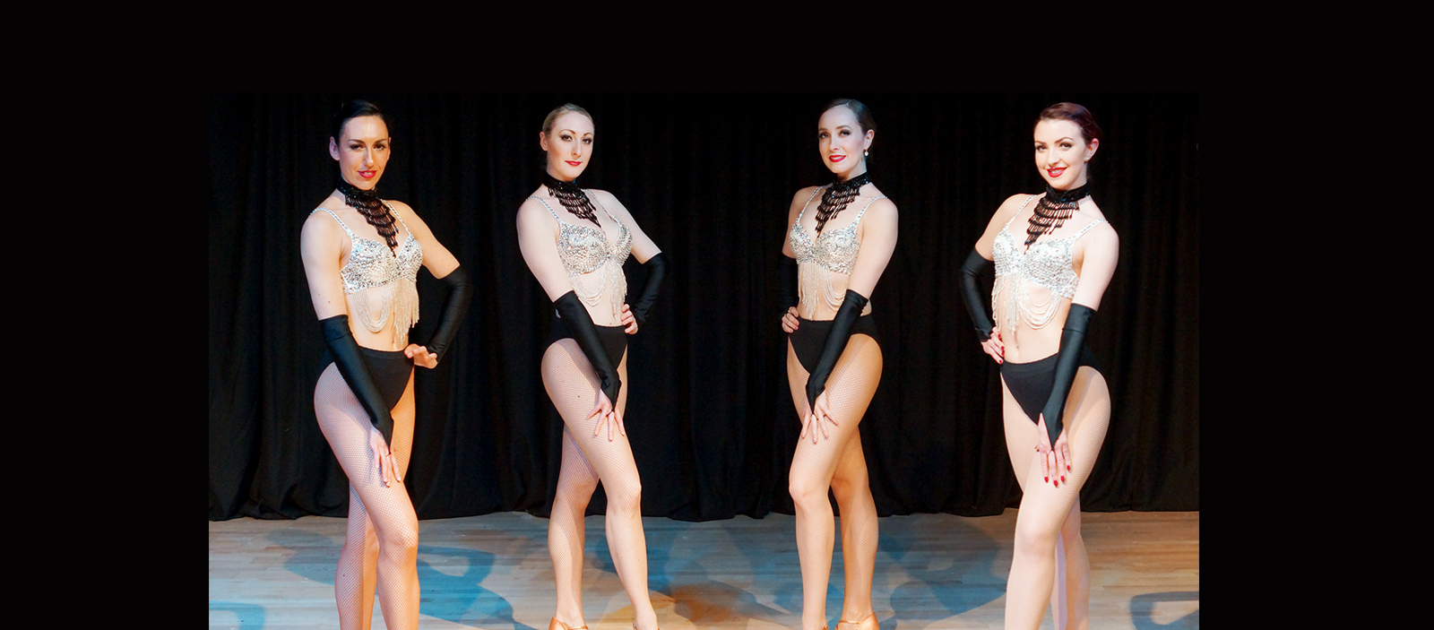 Female dancers in black and gold costumes